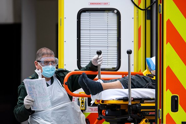 An NHS worker wearing a mask and goggles takes a man with an unknown condition from an ambulance at the St Thomas' Hospital on March 31, 2020 in London, England. | Photo: Getty Images