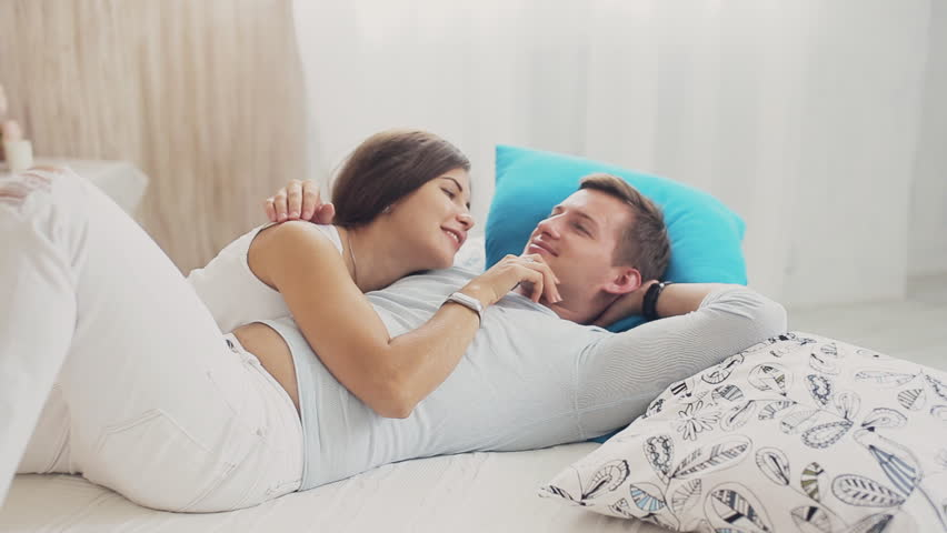 Cute couple cuddling and talking on the bed | Source: Shutterstock