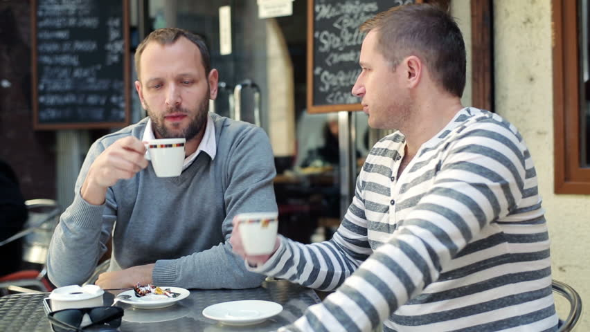 Two male friends drinking coffee at a coffee shop | Source: Shutterstock