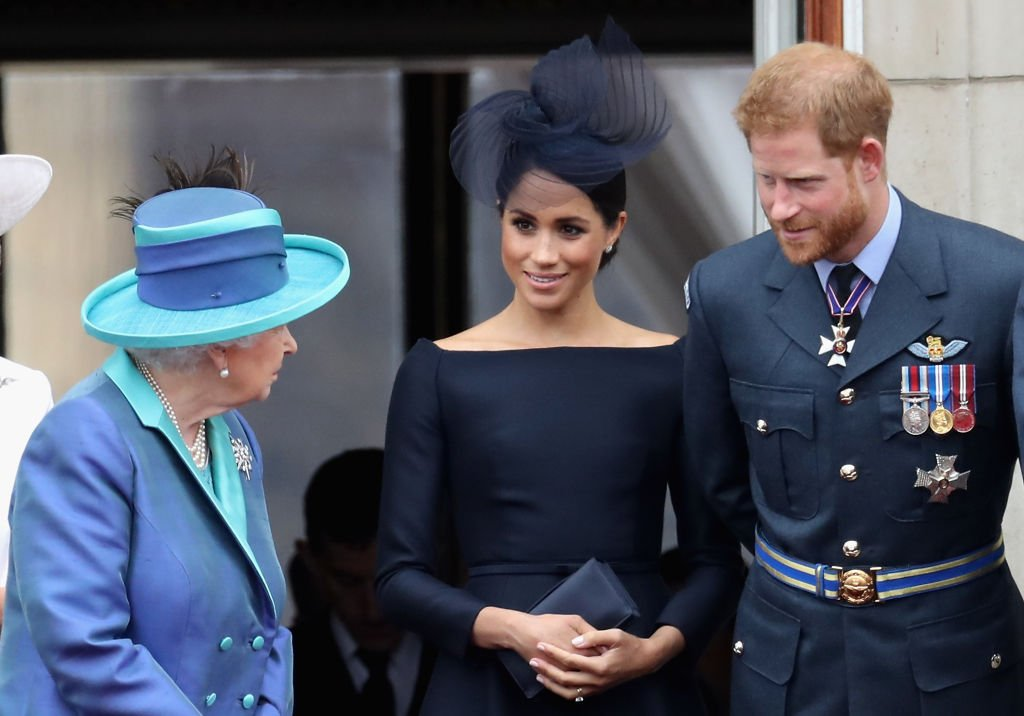 Queen Elizabeth II, Meghan Markle, and Prince Harry watch the RAF flypast on the balcony of Buckingham Palace on July 10, 2018, in London, England. | Source: Getty Images.