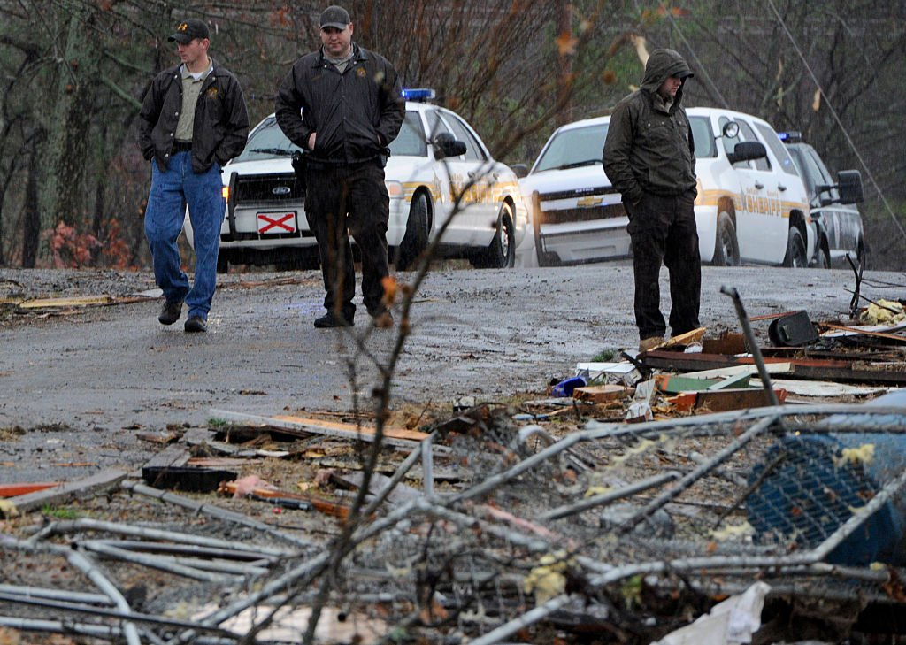 DeKalb County Sheriff's Deputies stand watch next to a log home which was destroyed by a tornado in the early morning hours on November 30, 2016 | Photo: Getty Images