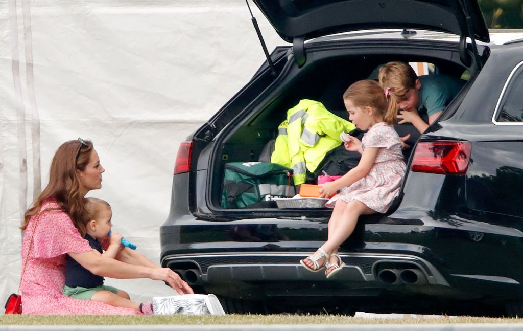 Kate Middleton sits on the grass with Prince Louis while Princess Charlotte and Prince George eat a snack in an SUV at the King Power Royal Charity Polo Match, at Billingbear Polo Club on July 10, 2019, in Wokingham, England | Source: Max Mumby/Indigo/Getty Images