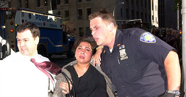 Police officer helps a woman get away from the dangerous events unfolding during the 9/11 terror attacks   Photo: Twitter/PAPD911 & Getty Images