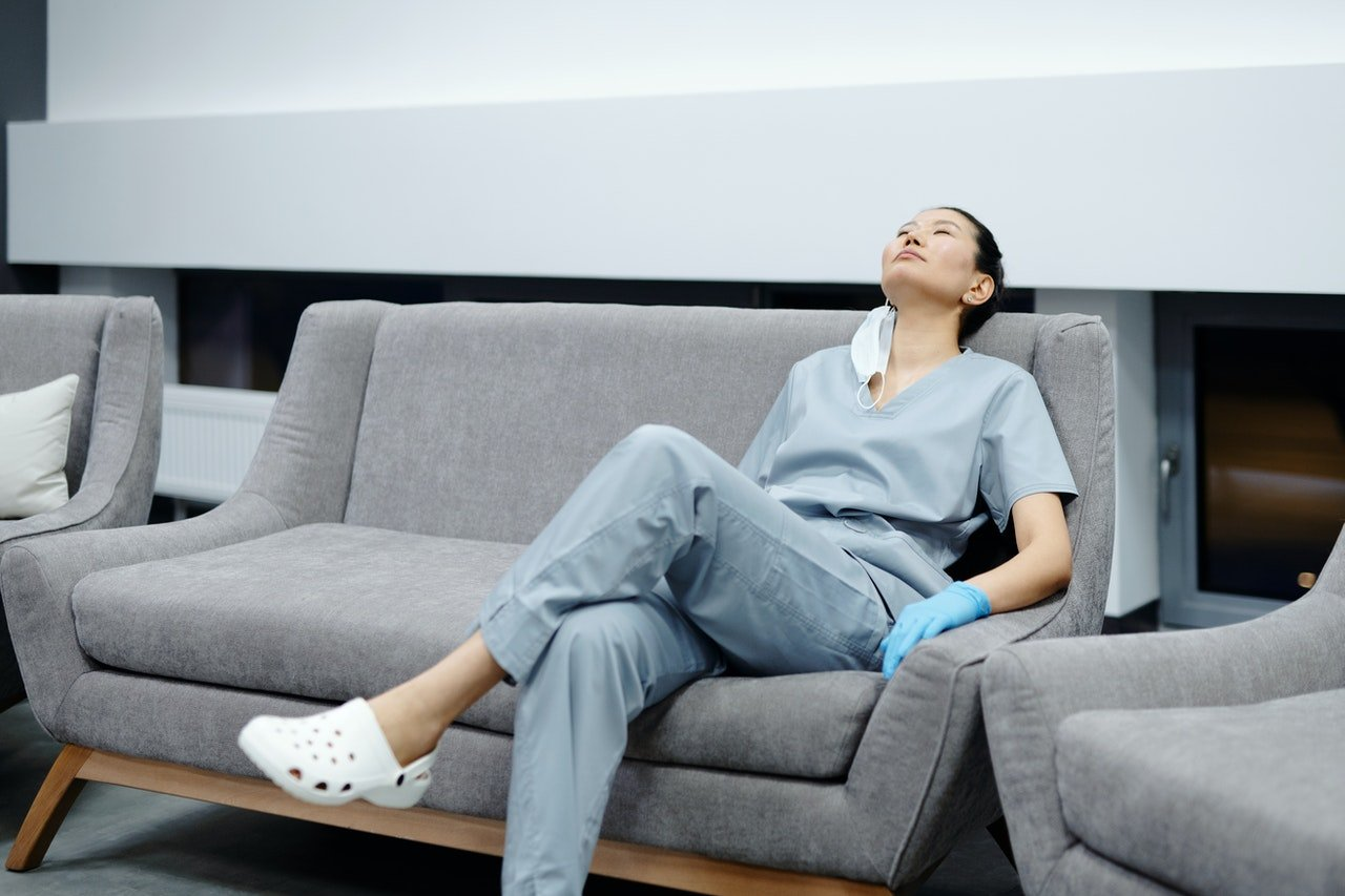 Photo of a tired nurse sitting on a couch | Photo: Pexels