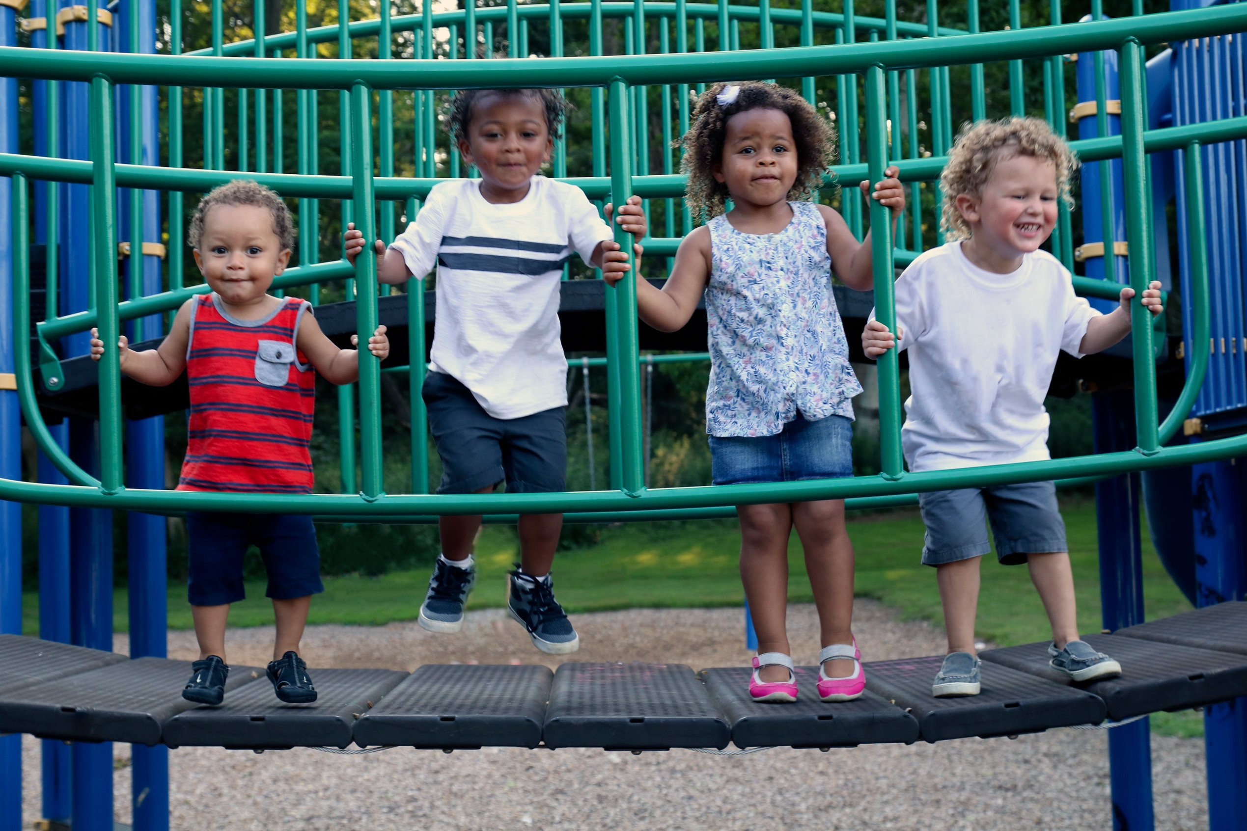 A diverse group of four children are playing together at the park | Photo: Shutterstock.com