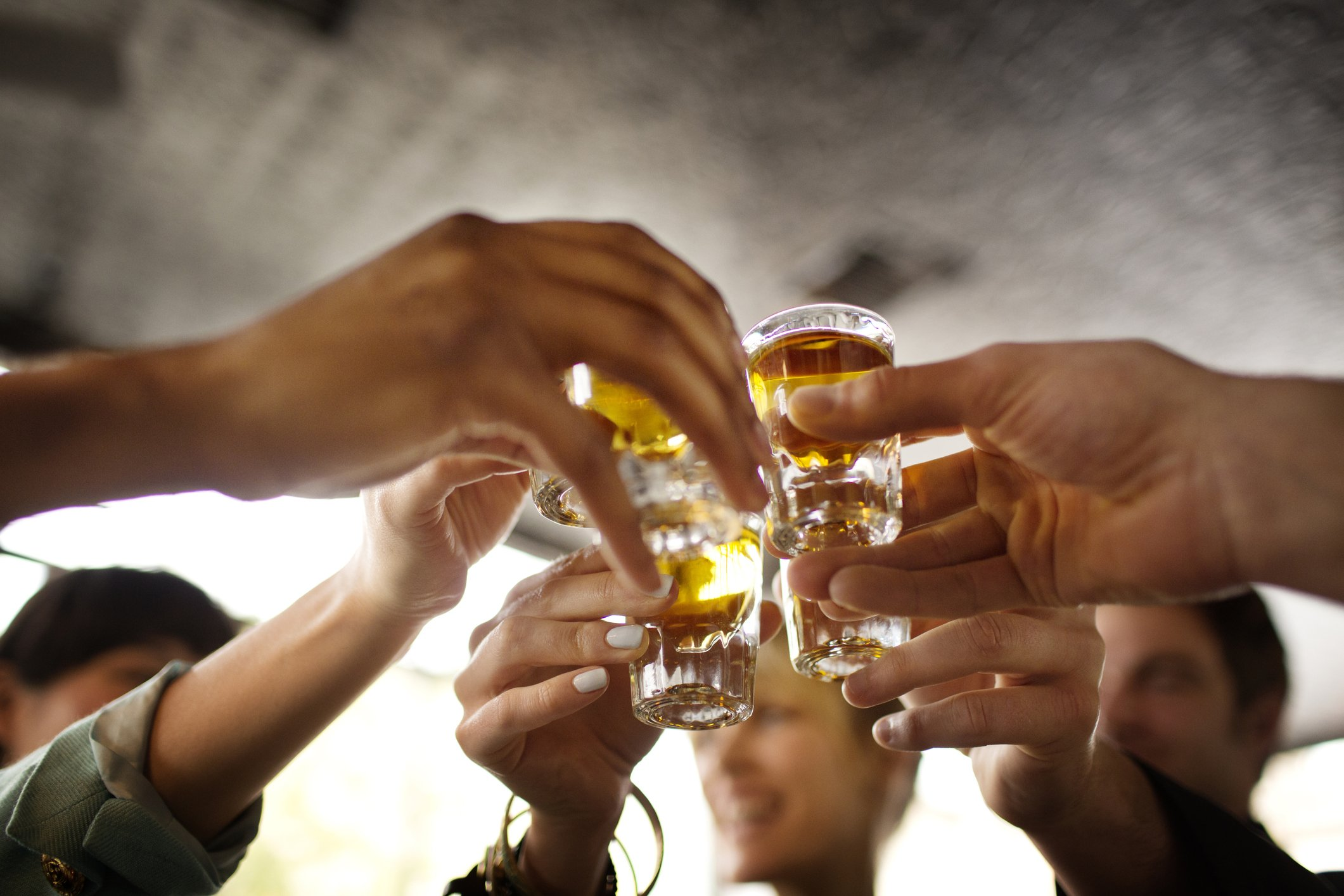 Friends toasting with shots of tequila in a bar.   Photo: Getty Images