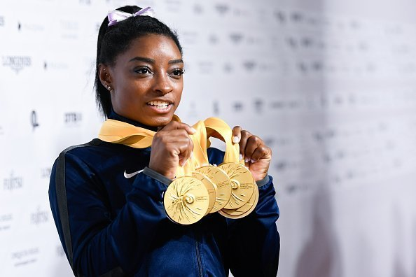 Simone Biles from the USA holding 5 gold medals in her hands.| Photo: Getty Images.
