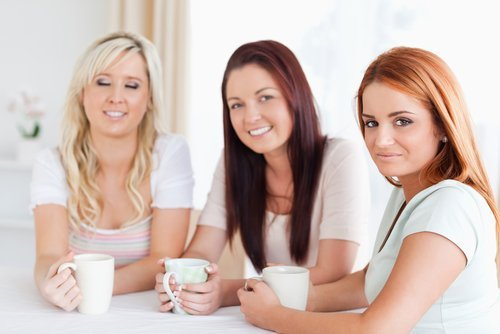 Three young women drinking coffee while talking. | Source: Shutterstock.