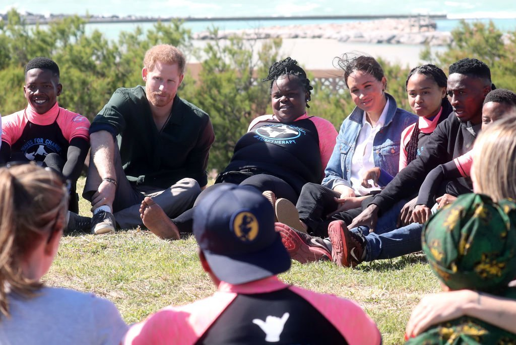 Prince Harry and Meghan Markle join surf mentors and participate in a group activity as they visit Waves for Change, an NGO, at Monwabisi Beach. | Source: Getty Images