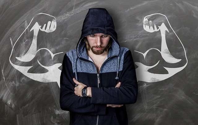 Man in hoodie stands in front of muscled strong arms drawing on board | Photo: Pixabay
