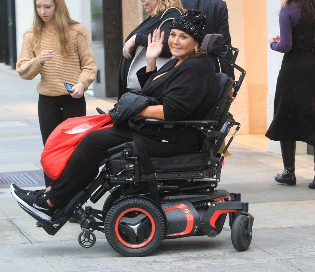Abby Lee Miller waves from her wheel chair as she is pictured by paparazzi on December 4, 2019, in Los Angeles, California | Source: Getty Images (Photo by SMXRF/Star Max/GC Images)