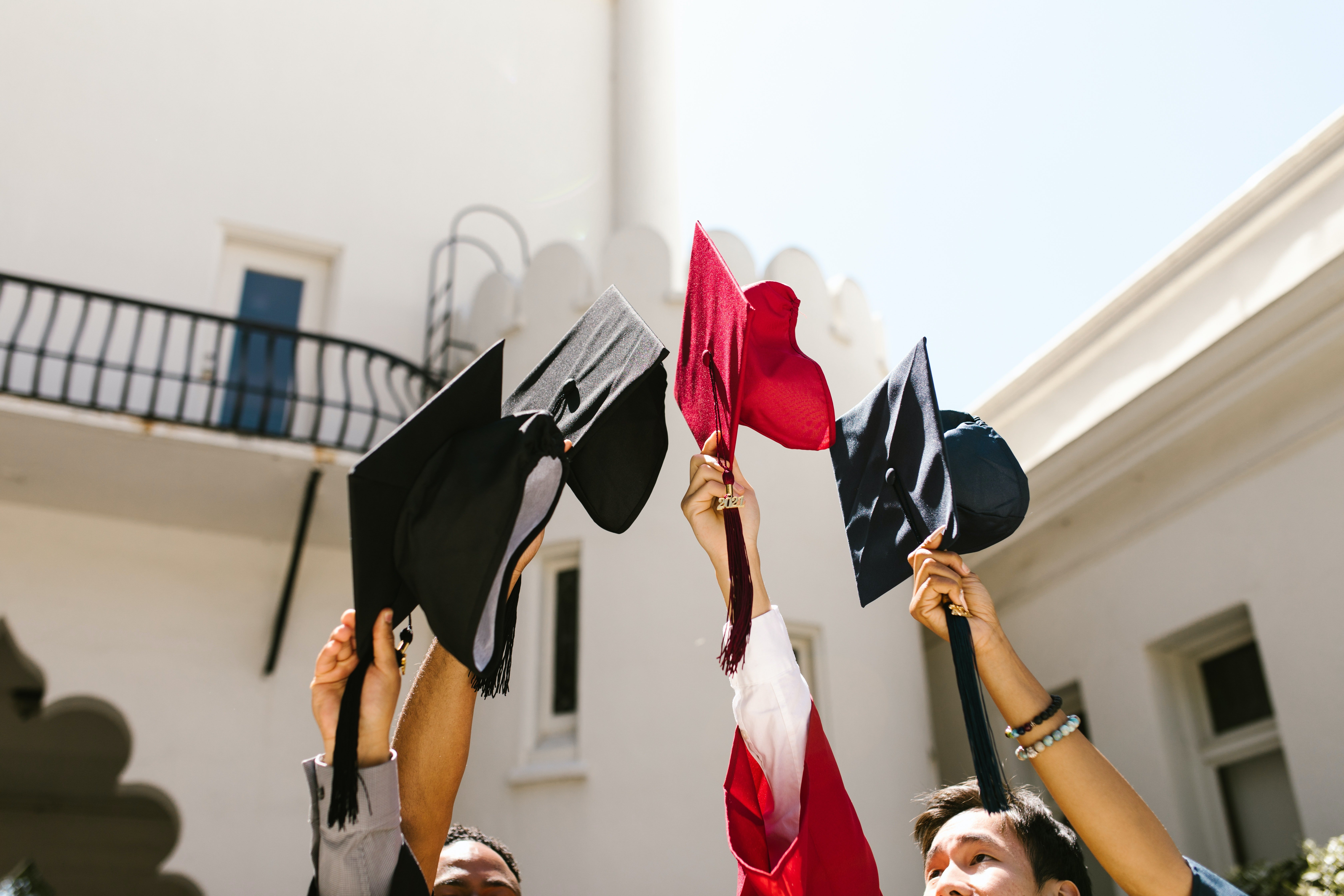 Graduating students holding up their caps. | Photo: Pexels