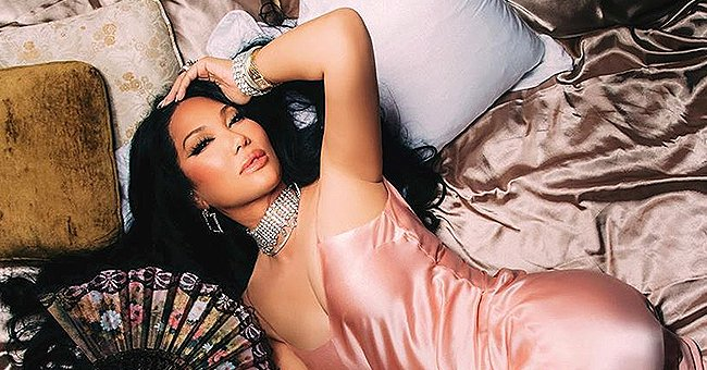 Kimora Lee Simmons Poses on a Bed & Looks Cool in a Pink Silk Dress with Sparkly Jewelry