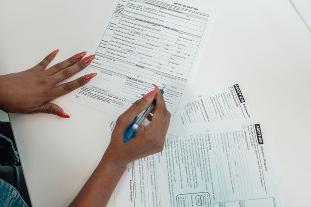 Person filling out adoption papers | Source: Pexels