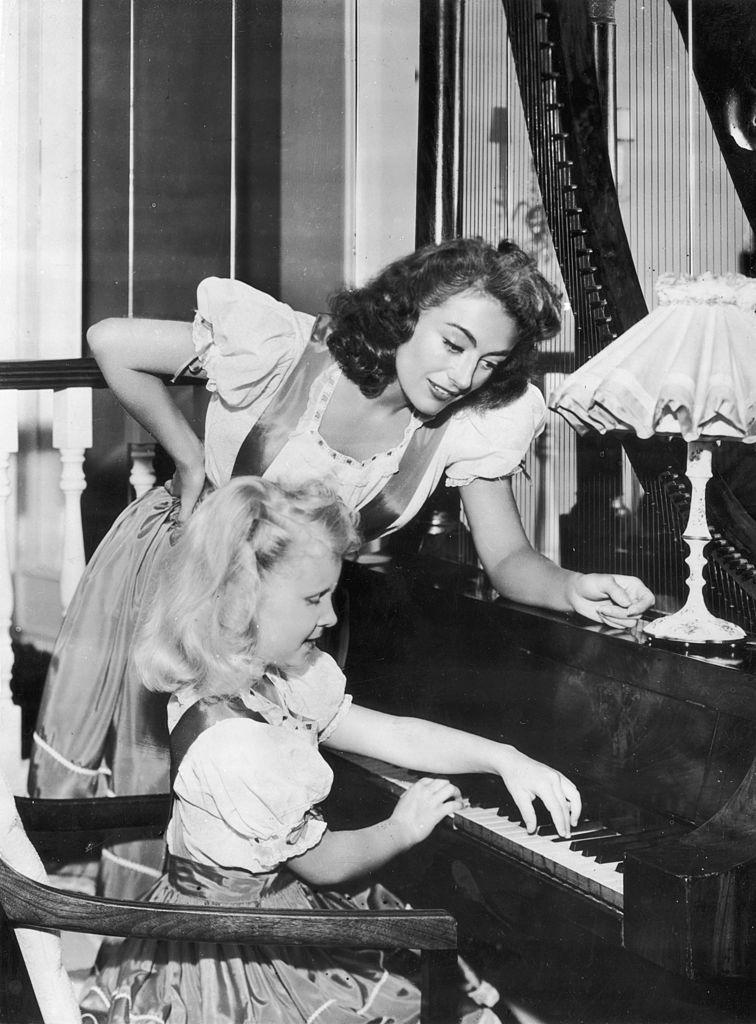Joan Crawford y su hija Christina tocando el piano.| Fuente: Getty Images