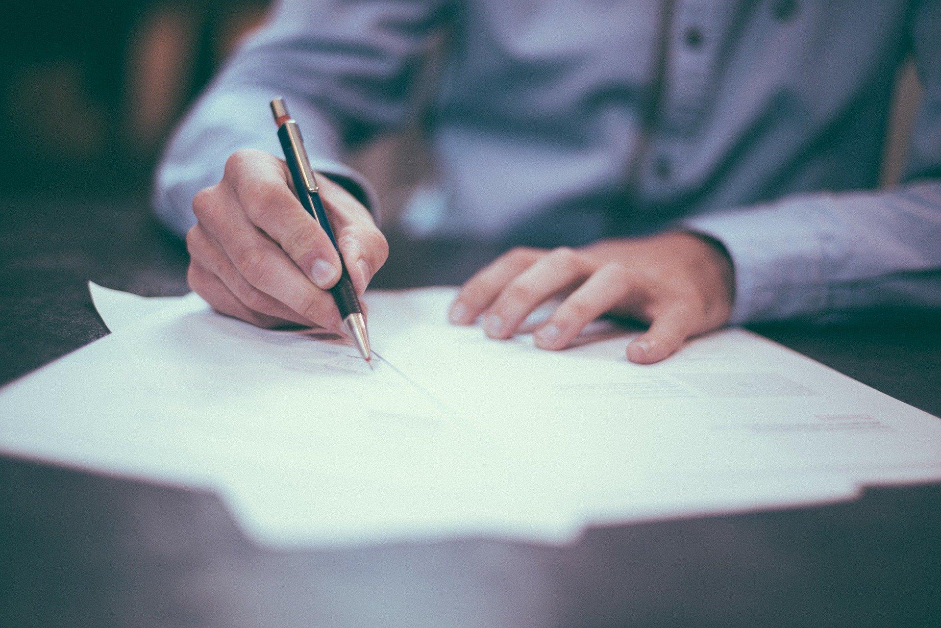 Man signing papers.     Photo: Pixabay