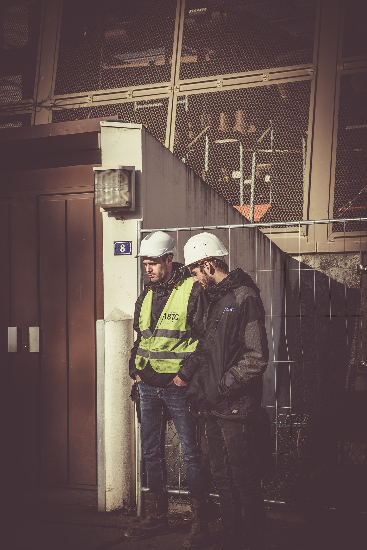 Two construction workers having a discussion   Photo: Pexels