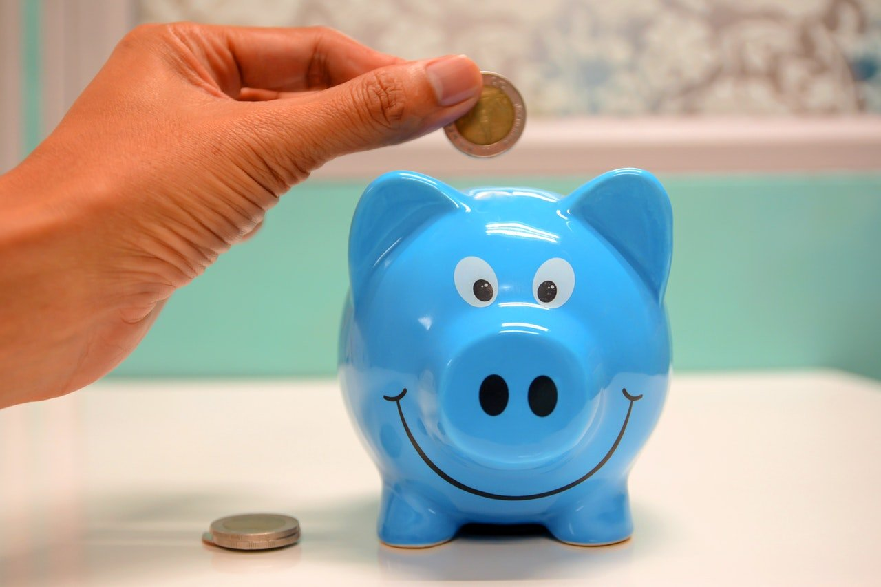 Photo of a hand dropping a coin in a piggy bank | Photo: Pexels