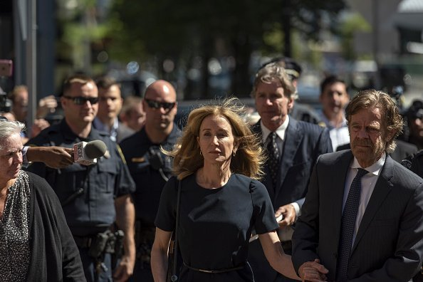 Felicity Huffman, center, arrives at federal court with her husband actor William H. Macy in Boston | Photo: Getty Images