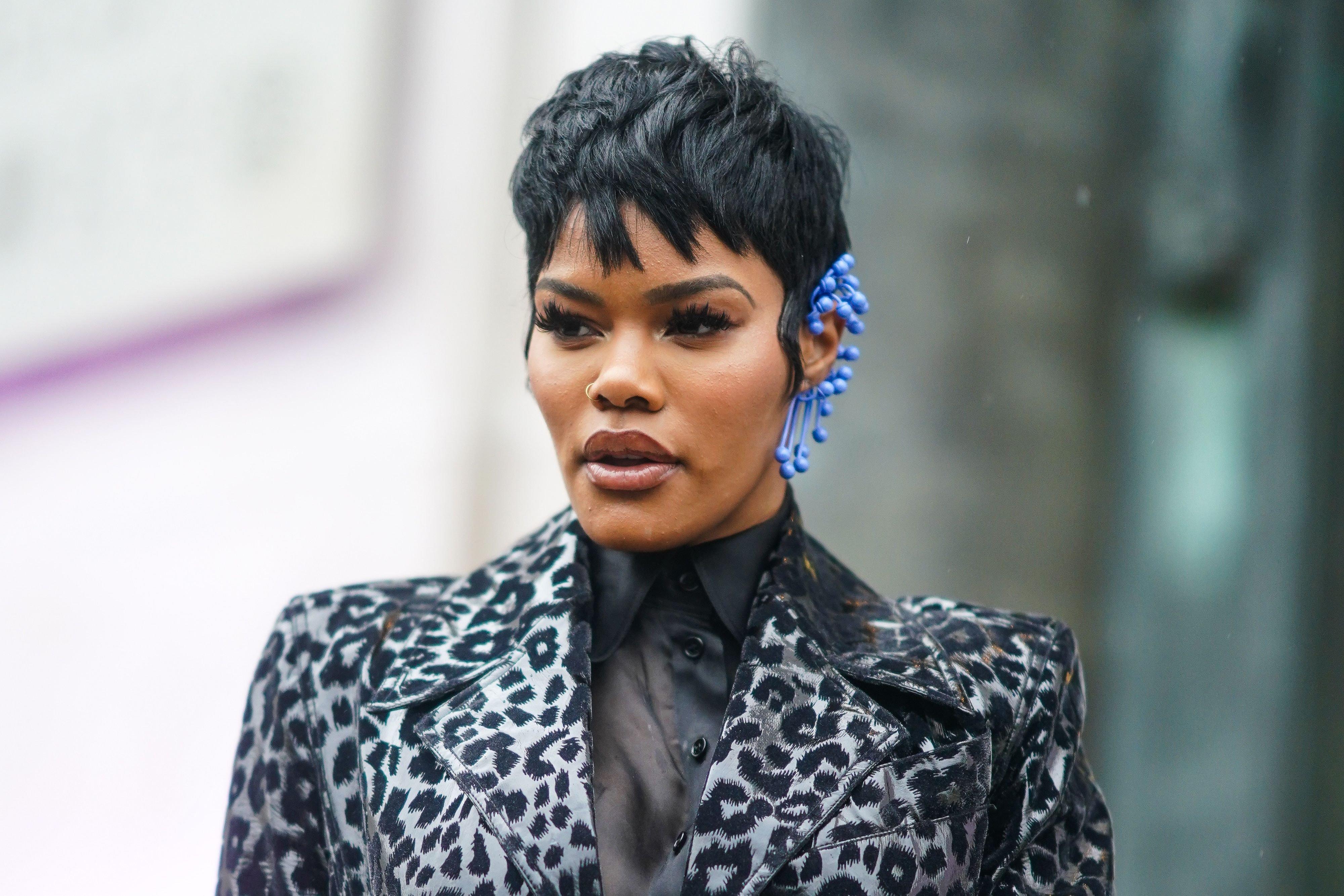 Teyana Taylor wears a black shirt, a long black and gray leopard print trench coat and a blue earring outside Mugler at Paris Fashion Week on February 26, 2020 | Photo: Getty Images