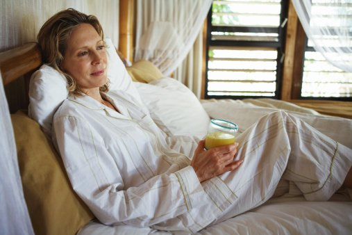Photo of woman with orange juice in bed | Photo: Getty Images