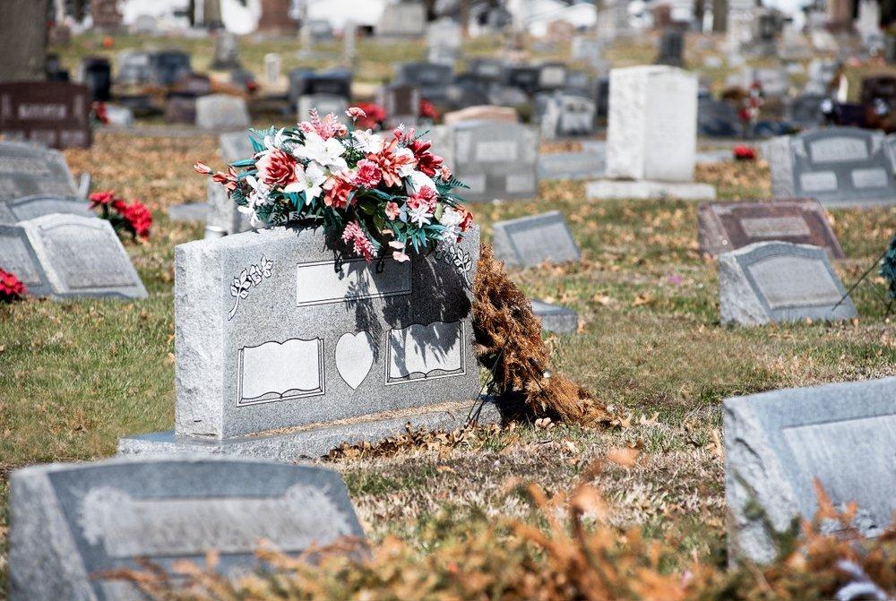 Pierre tombale dans un cimetière avec des fleurs et plus de pierres tombales en arrière-plan. | Shutterstock