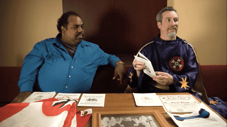 """Daryl Davis talking with a person wearing a Ku Klux Klan cloak in the trailer of the documentary film """"Accidental Courtesy"""" 