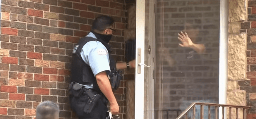 A screenshot of a policeman checking with witnesses who saw what happened to the baby who was abandoned in a Northwest Side alley in Chicago | Photo: Youtube/WGN News