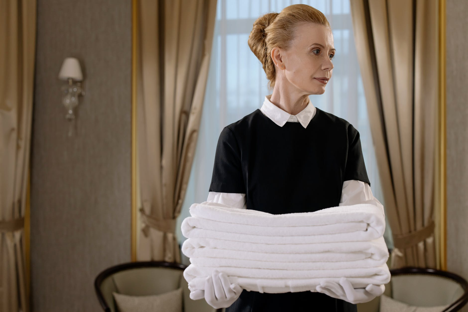 A housemaid carrying a pile of folded towels | Source: Pexels