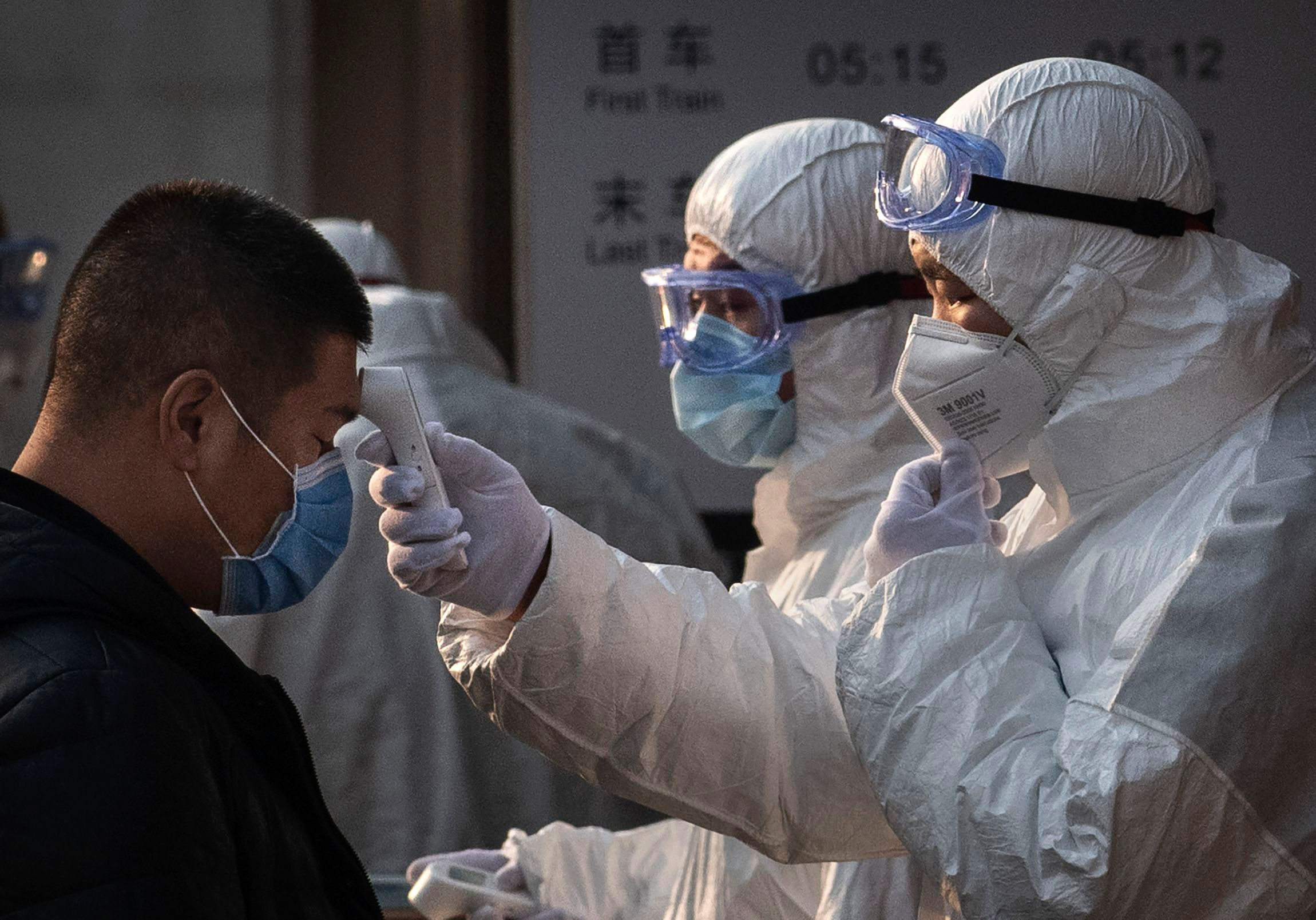 A health worker checks the temperature of a woman entering a subway station on January 25, 2020 in Beijing, China.   Source: Getty Images