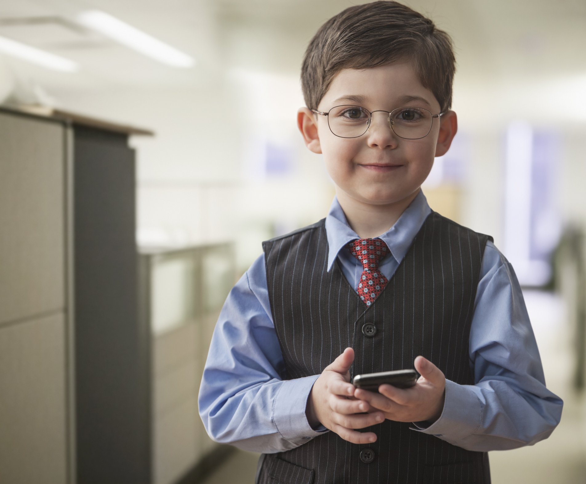 Photo of boy wearing businessman outfit in office   Photo: Getty Images