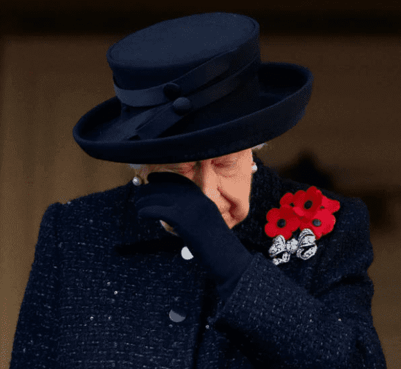 Queen Elizabeth wipes away tears while standing on a balcony watching the Remembrance Sunday service at The Cenotaph on November 10, 2019, in London, England | Source: Max Mumby/Indigo/Getty Images