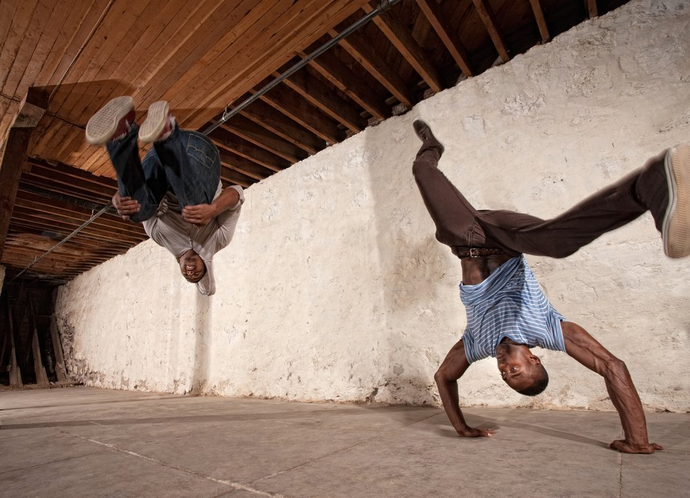 Two men doing headstands and backflips. | Photo: Shutterstock