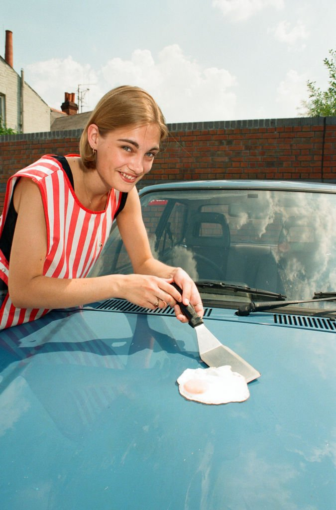 A girl frying an egg on top of car hood amidst a hot summer, circa 1995   Source: Getty Images