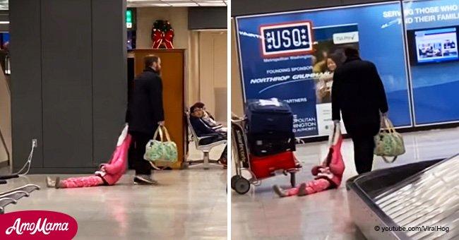 Ein müder Vater trägt seine Tochter an einem Flughafen auf eine kreative Weise