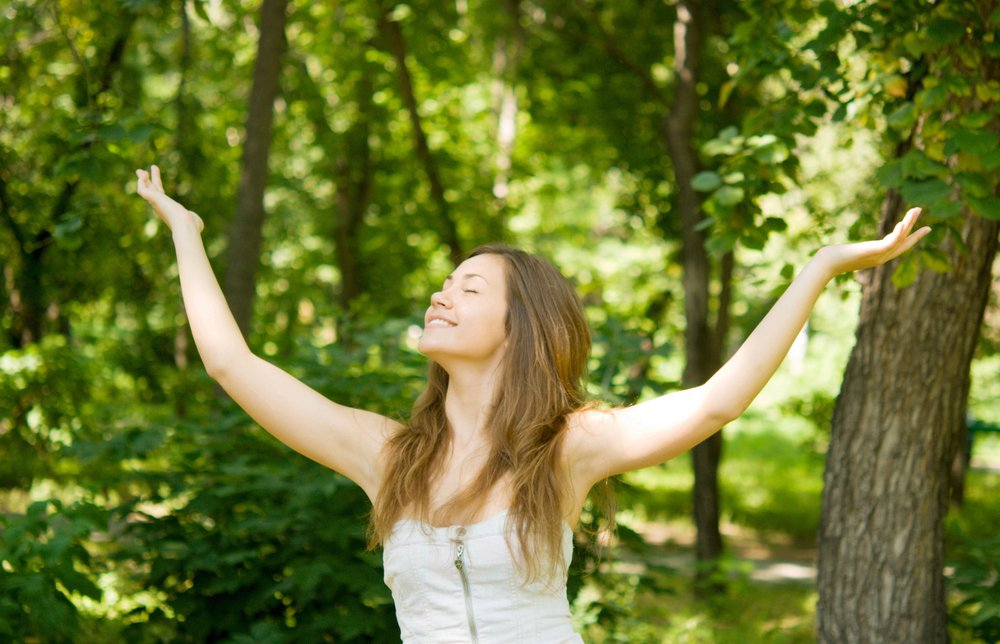A pretty woman laughing in the woods   Photo: Shutterstock