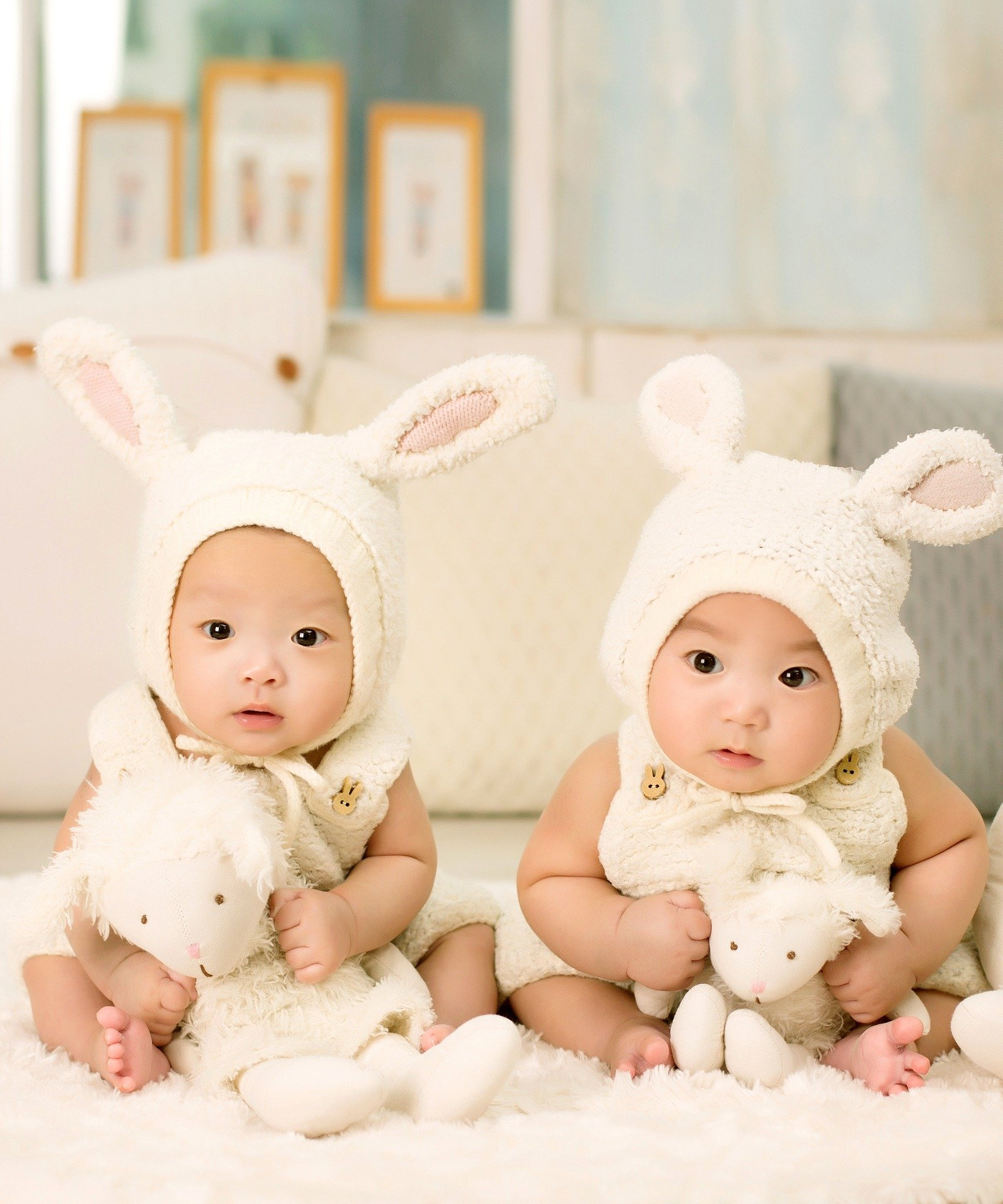 Pictured - A photo of twins wearing bunny outfits and holding on to their toys   Source: Pixabay