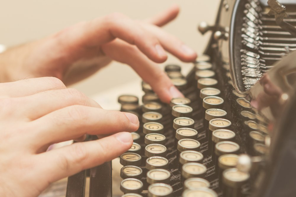 Hands writing on old typewriter | Shutterstock
