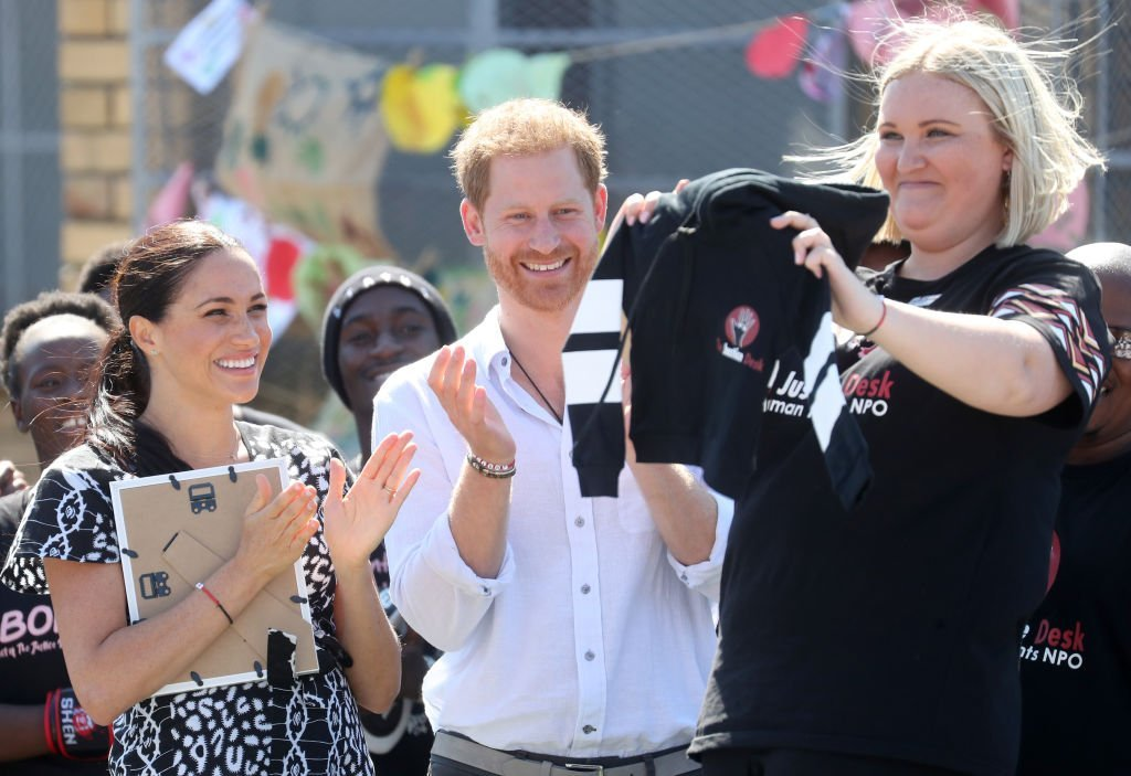 Meghan Markle and Prince Harry laugh with Jessica Dewhurst, Justice Desk Founder  during their visit to a Justice Desk initiative in Nyanga township. | Source: Getty Images