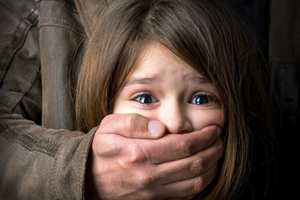 Adult man's hand covering scared young girl's mouth | Photo: Shutterstock