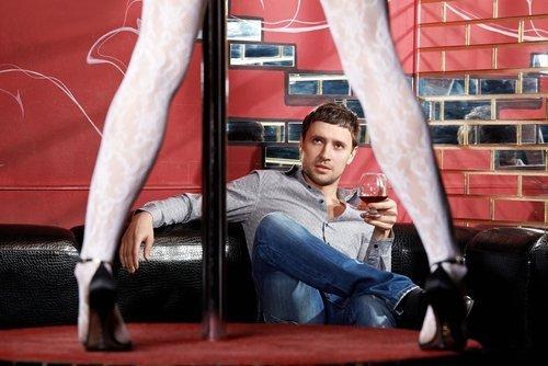 Un homme avec un verre de vin rouge dans un club de strip-tease. | Source : Shutterstock.