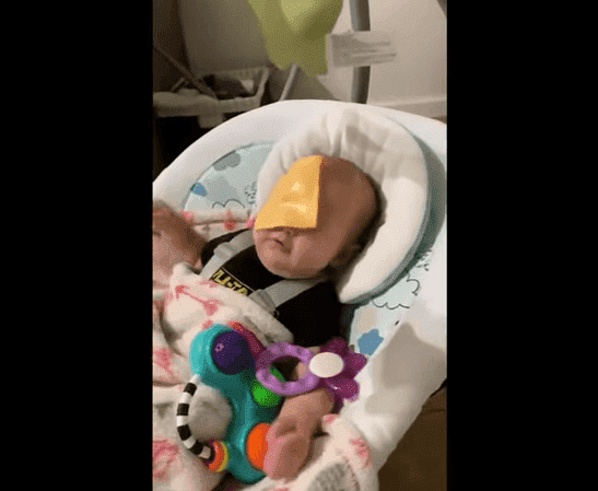 A baby with a slice of cheese stuck to his face | Photo: TopVids!
