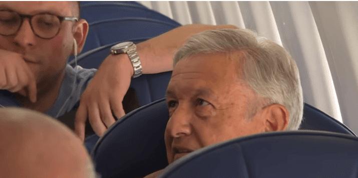AMLO en compañía de dos personas, dentro del avión. | Imagen: YouTube / AFPES