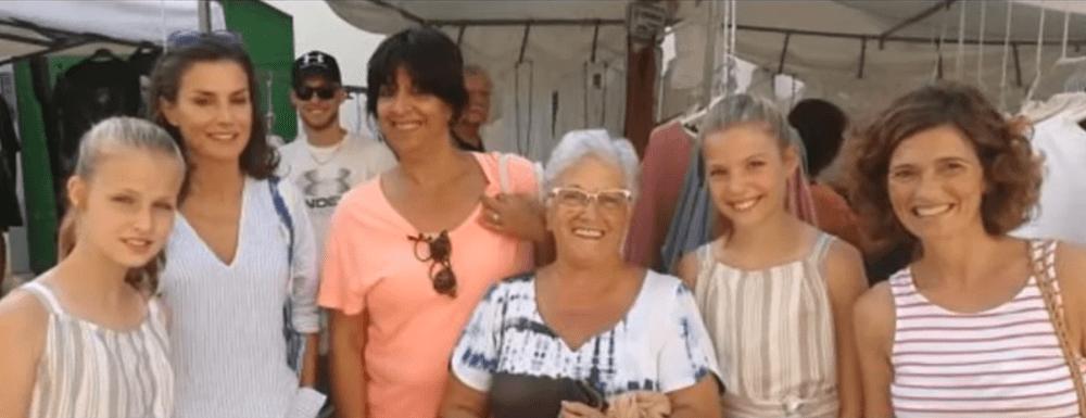 La reina Letizia de España y sus hijas, la princesa Leonor y la infanta Sofía, acompañadas pr lugareños en las calles de Pollença, en Mallorca. | Imagen: YouTube/EL ATICO BB