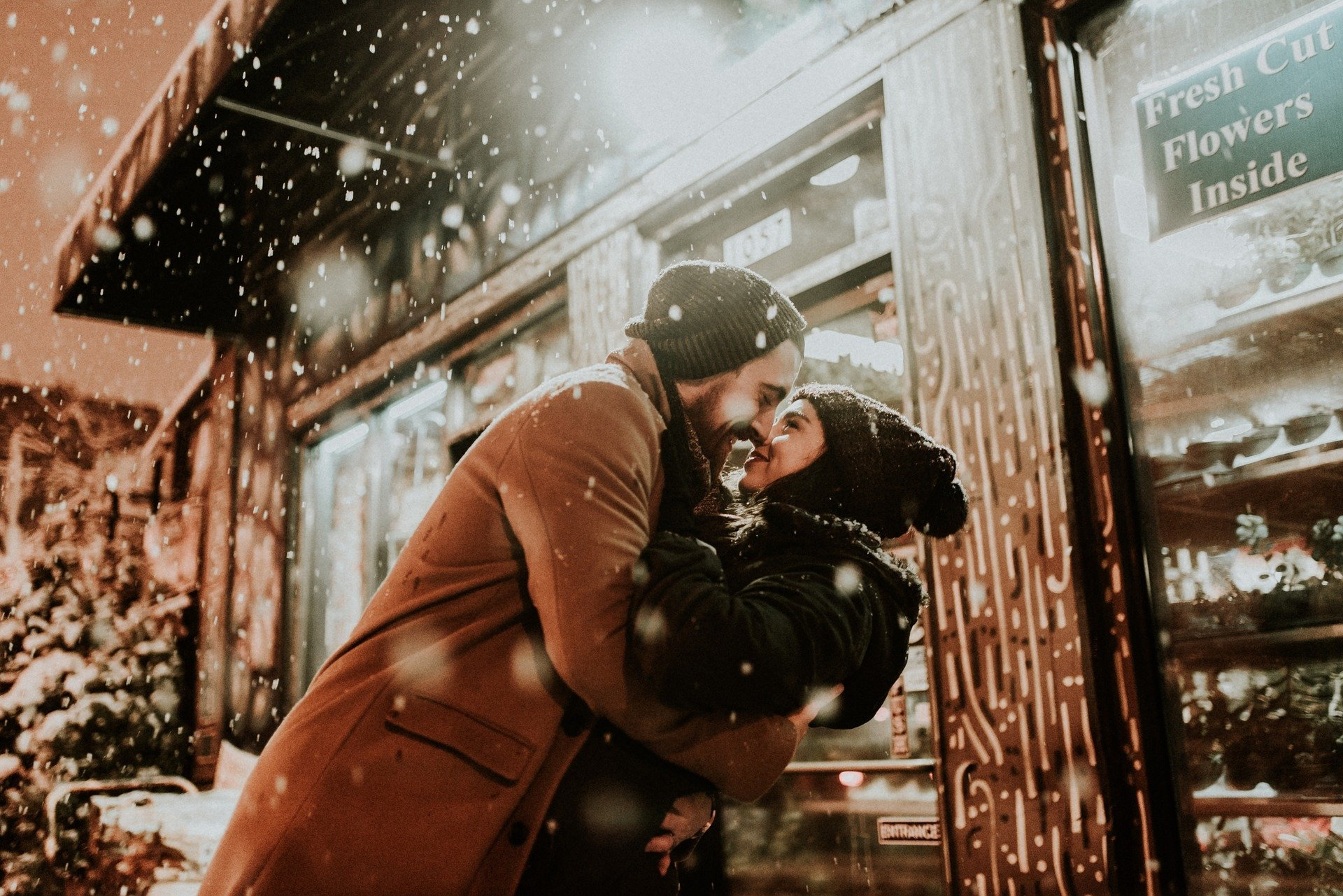 A couple embracing outside a flower shop while it snows   Photo: Pixabay/StockSnap