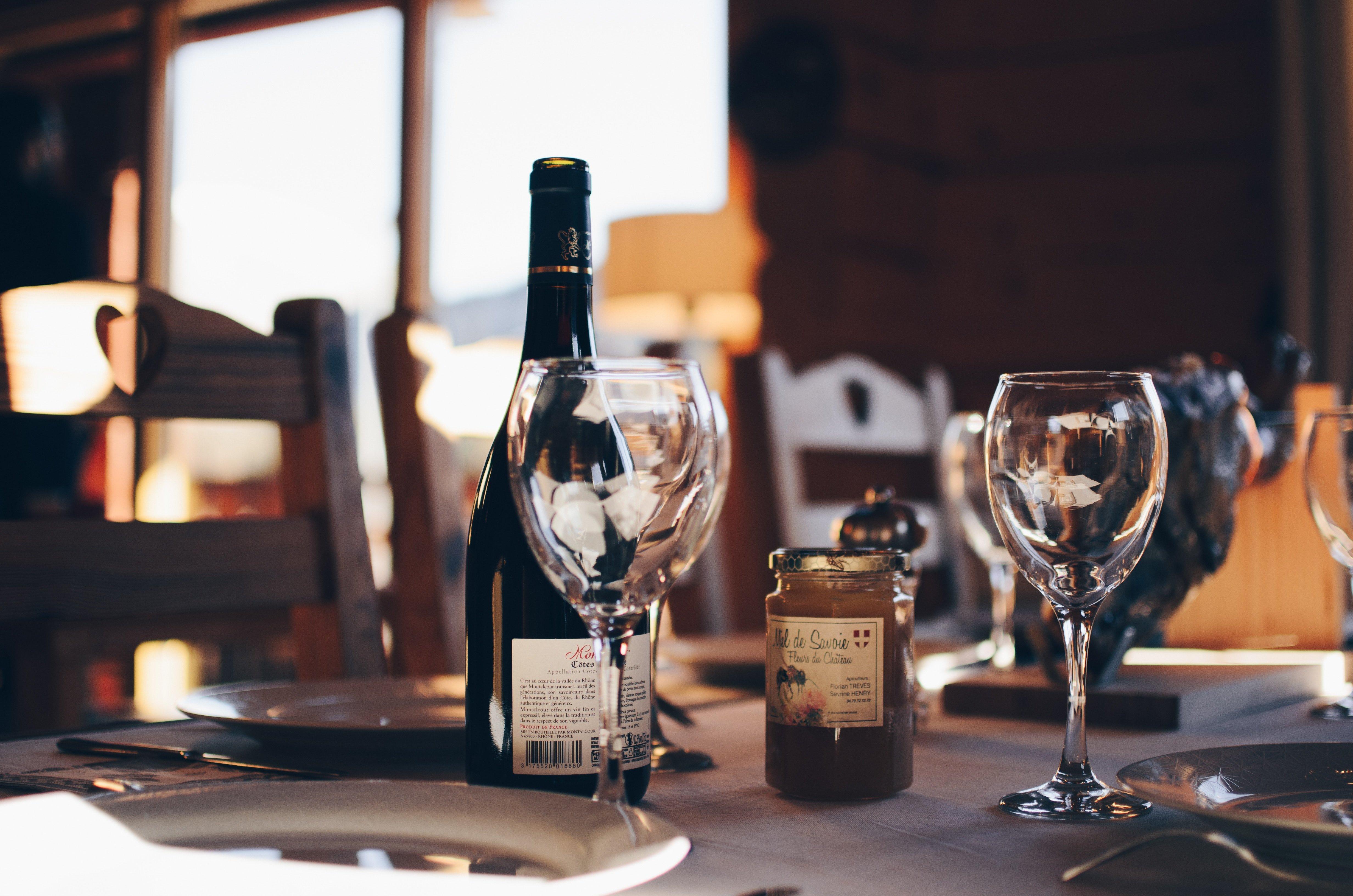 Une photo de deux verres à vin vides et d'une bouteille de vin | Source : Unsplash