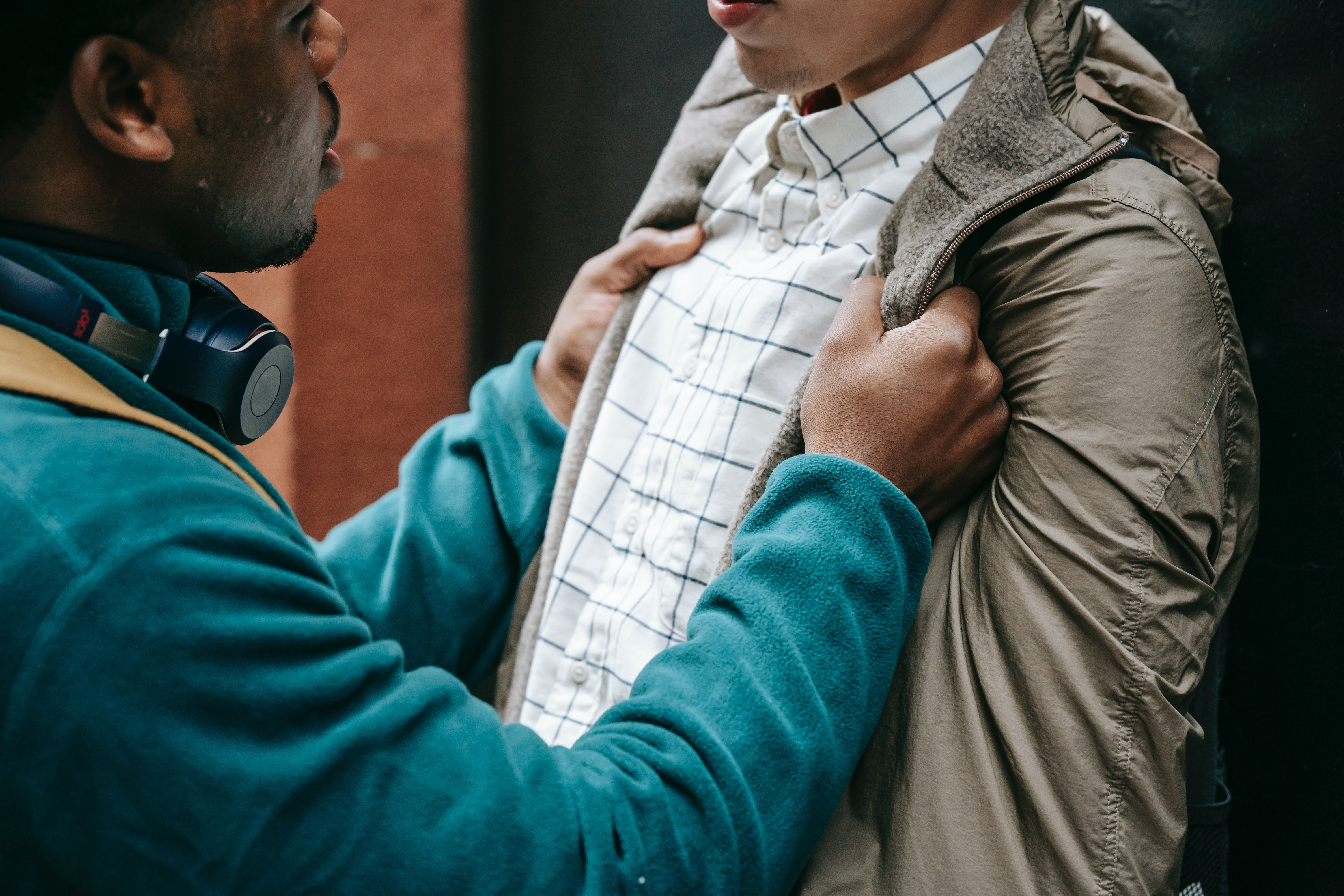 A man grabbing another man by his jacket.   Photo: Pexels