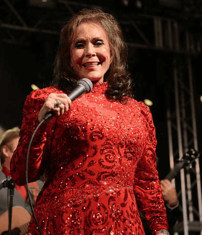 Singer Loretta Lynn holds up a microphone as she performs onstage at Stubbs, on March 17, 2016, in Austin, Texas | Source; Scott Dudelson/Getty Images