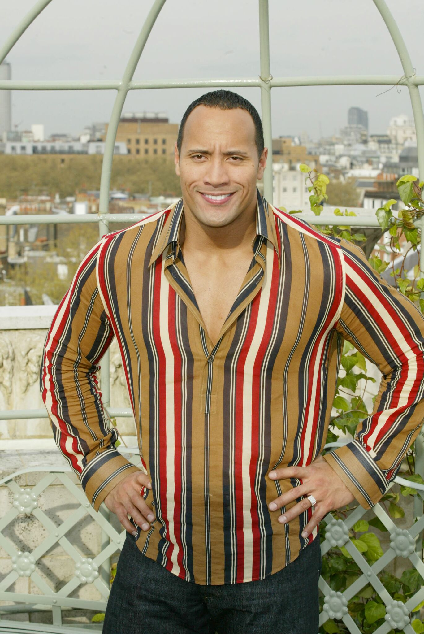 Wrestler and actor The Rock (real name Dwayne Johnson) smiles for the cameras during a photocall to promote his new movie The Scorpion King | Getty Images