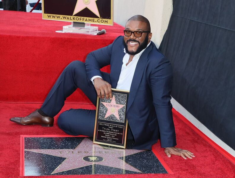 Tyler Perry posing beside his Hollywood Star | Source: Getty Images/GlobalImagesUkraine